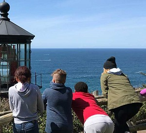 kids looking out at the ocean at a lighthouse